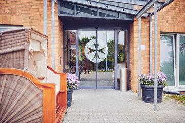 Glastür-Eingang mit Johanniter Logo, links vor dem Eingang steht ein Strandkorb