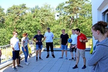Eine Gruppe von Jugendlichen spielt unter Anleitung eines jungen Erwachsenen im Johanniter-Jugend-Polo Ball