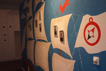 Bemalte Wand mit Segelschiffen und dem Kompass-Logo