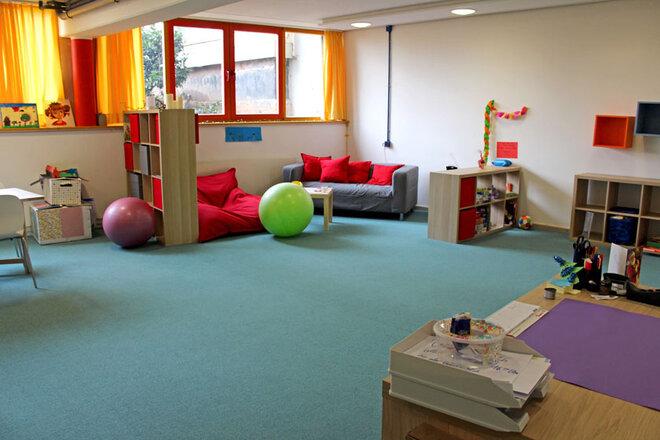 Gruppenraum mit gemütlicher Entspannungsecke, Spielen, Sitzgelegenheiten und Co.
