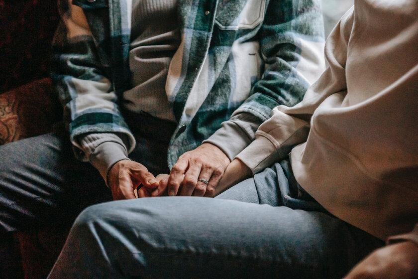 Zwei Menschen halten einander die Hände.