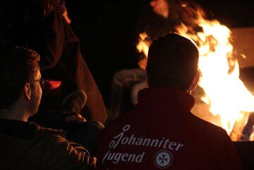 Zwei Jugendliche sitzen vor einem Lagerfeuer