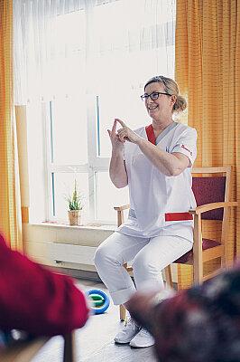 Eine blonde Frau erklärt den Anwesenden etwas in der Sportstunde