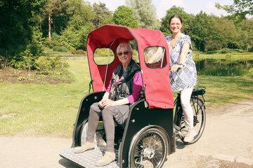 Eine ältere Frau wird von einer jüngeren Frau in einer Fahrrad-Rikscha durch einen Park gefahren