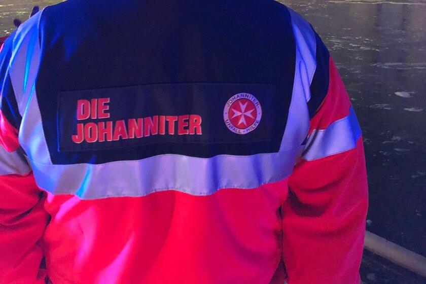 Johanniter Katastrophenhelfer von hinten in Einsatzkleidung.