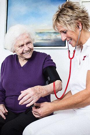 Eine Pflegerin misst bei einer älteren Dame den Blutdruck.