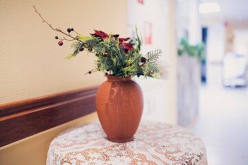 Weihnachtlich dekorierte Vase auf einem Tisch