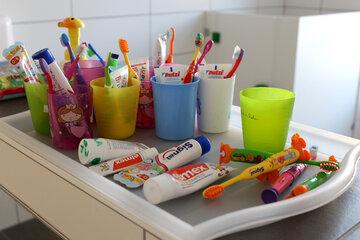 Viele kleine Zahnbürsten in bunten Farben sowie einige Kinderzahncremes liegen auf einem großen Tablett bzw. stehen in zugehörigen Zahnputzbechern.