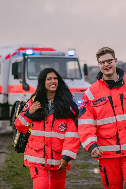 Zwei Personen in Johanniter-Einsatzkleidung stehen vor einem Unimog