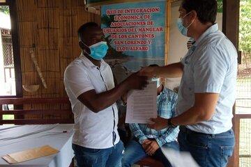 Der Vetreter des Umweltministeriums, Fernando Moya, übergibt das Abkommen an den Präsidenten von APESARBIPAR, Jackson Cabezas.