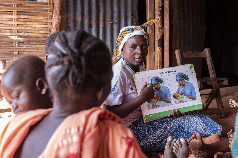 Eine Mutter mit einem Infoplakat über das Stillen klärt andere Mütter auf.