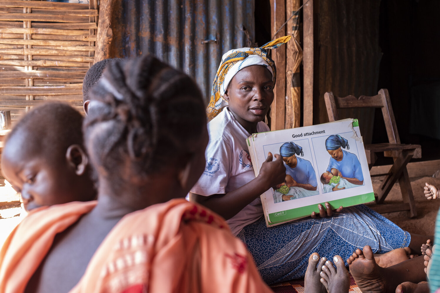 A mother with an information poster about breastfeeding educates other mothers