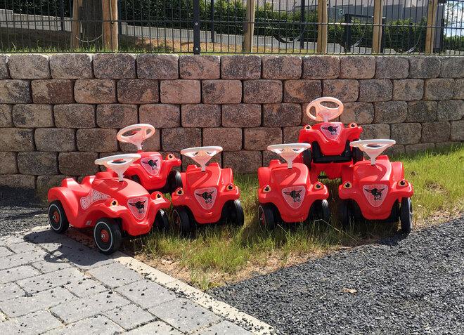 Sechs rote Bobby-Cars stehen in einer Reihe