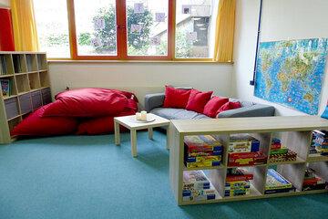 Sitzgelegenheit mit gemütlichen großen roten Kissen. Im Vordergrund ist ein Regal mit zahlreichen Gesellschaftsspielen zu sehen.