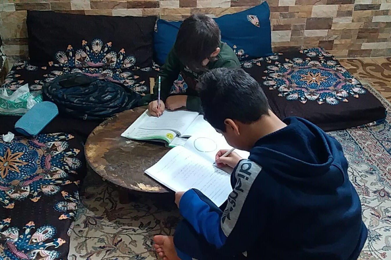 Ein Junge macht Hausaufgaben am Wohnzimmertisch