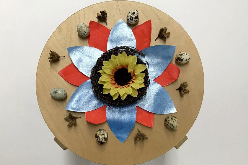 Pappvolage bereits kreativ gestaltet mit einer Sonnenblume, farbigen Blättern und Wachteleiern.