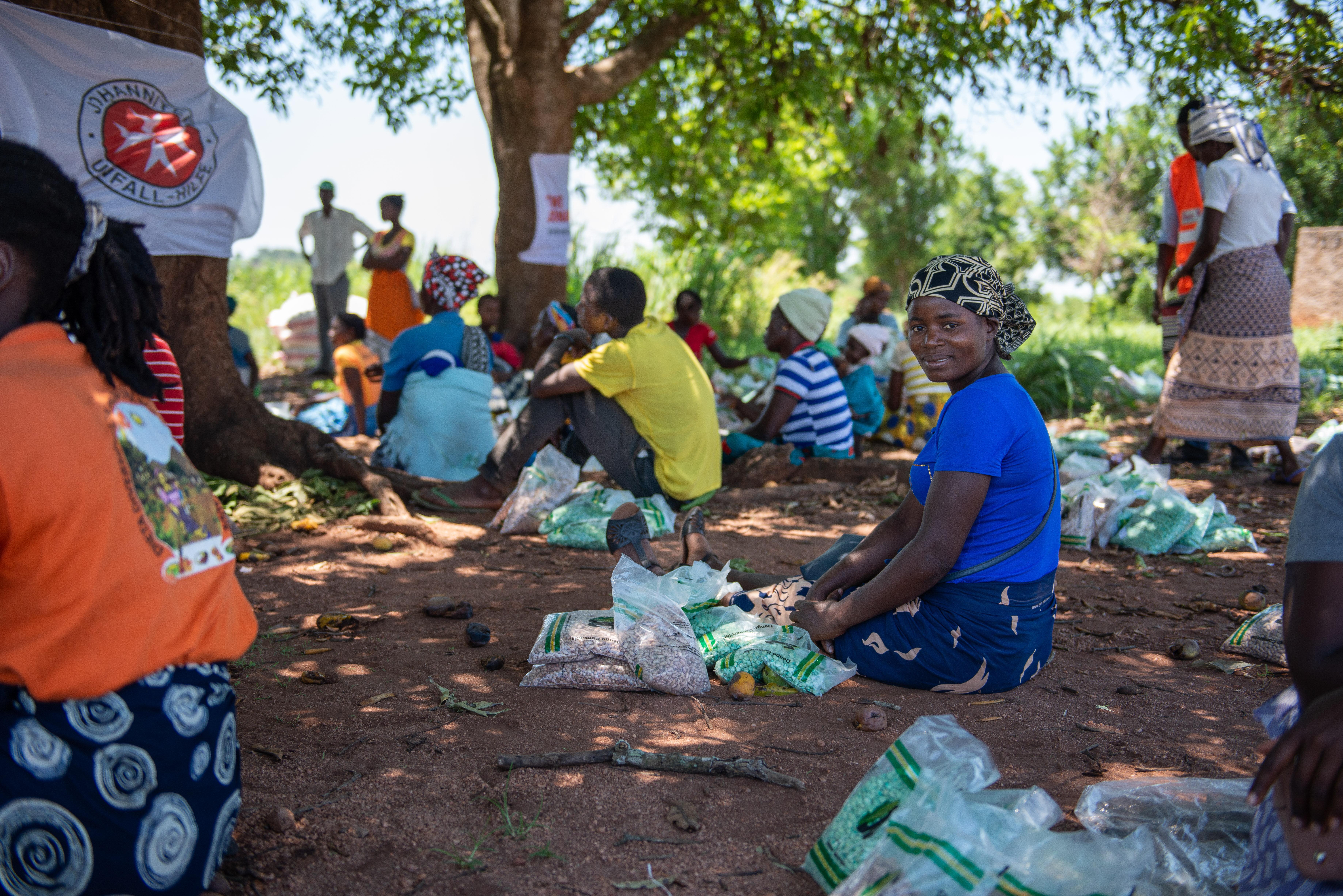 Eine Frau sitzt auf dem Boden, neben ihr liegt das von den Johannitern verteilte Saatgut