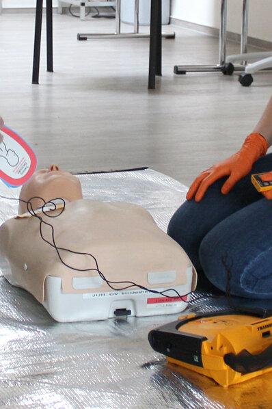 Man sieht wie jemand das AED anlegen möchte.