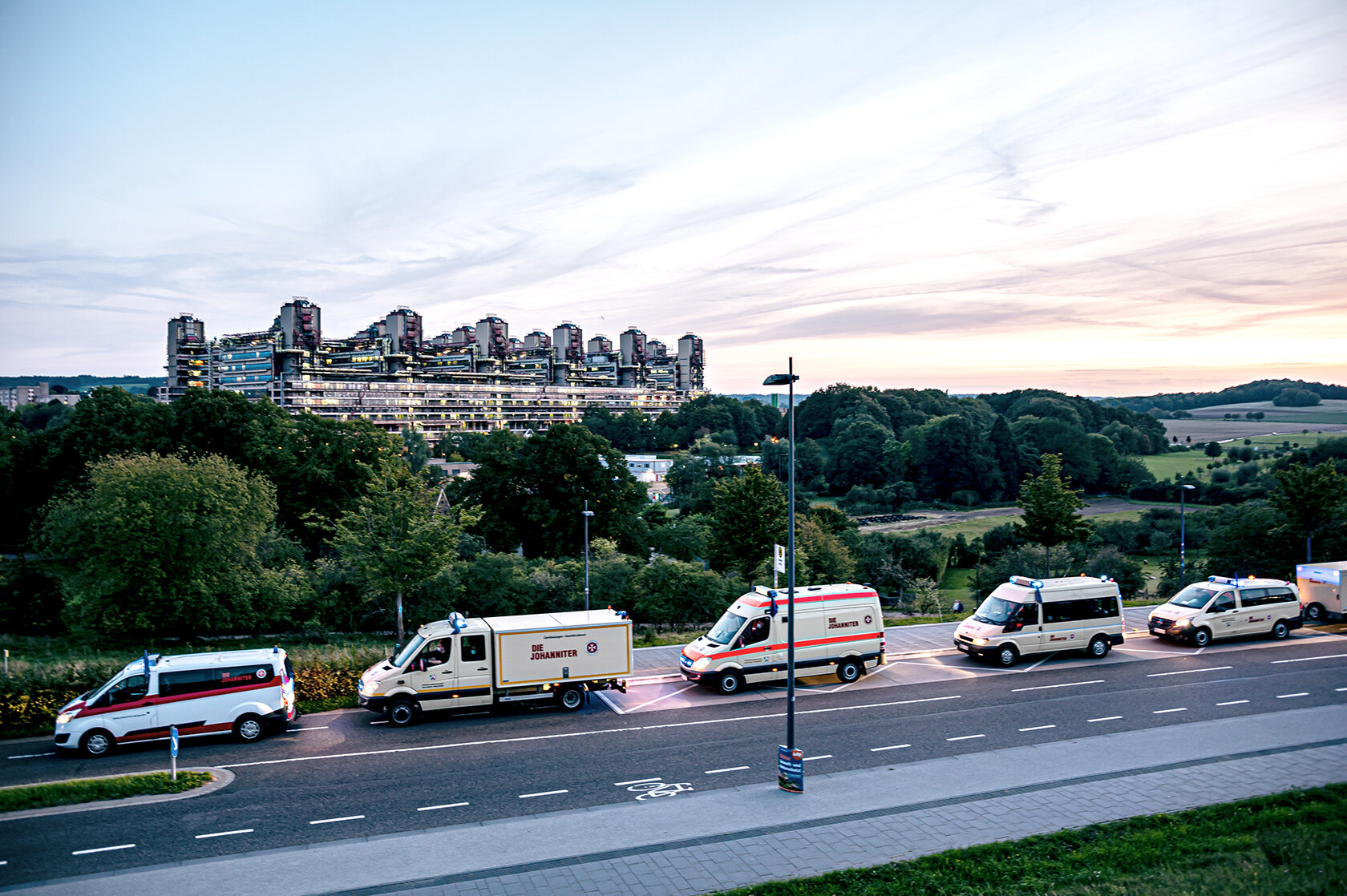 Einsatzfahrzeuge der Johanniter mit dem Aachener Klinikum im Hindergrund