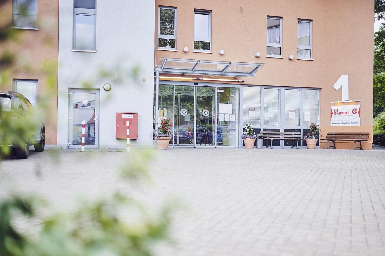 Vorplatz mit Gartenbank und Sicht zum Eingang des Johanniter-Hauses Köln Zollstock.