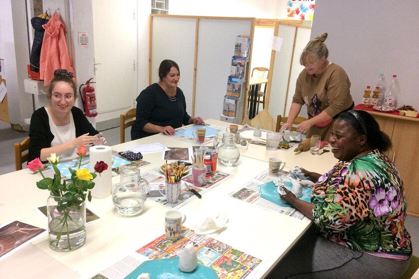 Gemeinsam sitzen die Teilnehmenden am Tisch und formen kleine Figuren wie Igel oder Schnecken aus weißem Ton.