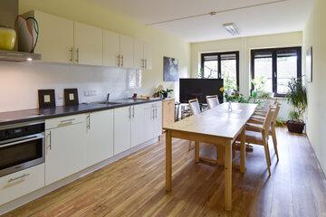 Große moderne helle Küche mit großen Holztisch und Stühle im Johanniterhaus Bonn.