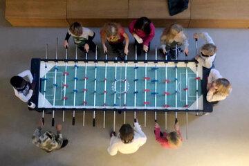 Kinder stehen um einen Kickertisch und spielen gegeneinander