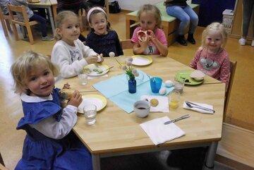 Fünf Kinder sitzen um einen Tisch und essen Brötchen und Brot.
