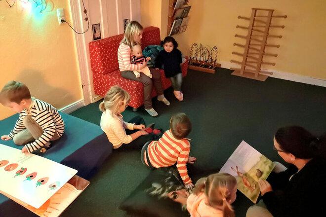 Die Kinder sitzen gemütlich im Gruppenraum und schauen sich Bücher an. An einer der Ecken sitzt eine Erzieherin, die gerade einem kleinen Mädchen vorliest.