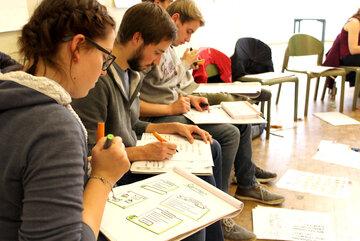 Junge Erwachsene sitzen nebeneinander und zeichnen auf einem Block