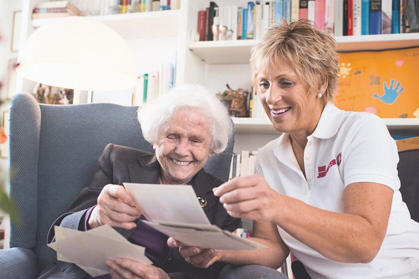 Eine Pflegerin sitzt auf der Armelehne des Sessels und schaut sich mit der Seniorin im Sessel einen Beipackzettel an.
