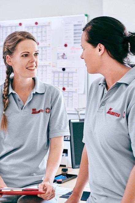 zwei Mitarbeiterinnen einer Johanniter-Sozialstation in grauen Poloshirts