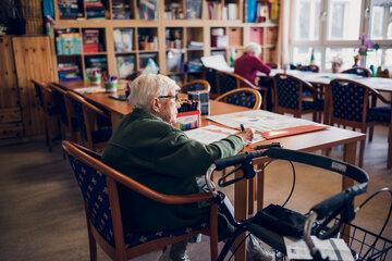 Zwei Bewohnerinnen malen an großen Tischen im Freizeitraum