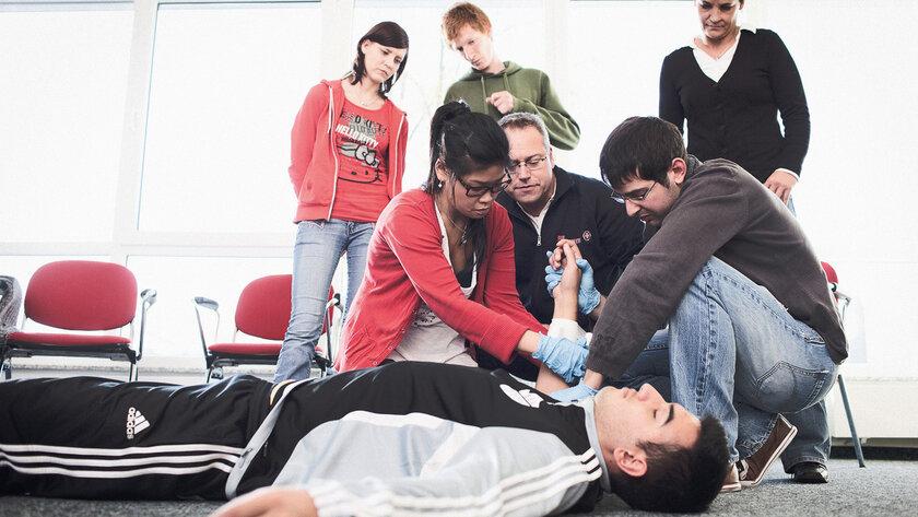 Teilnehmende eines Erste-Hilfe-Kurses trainieren