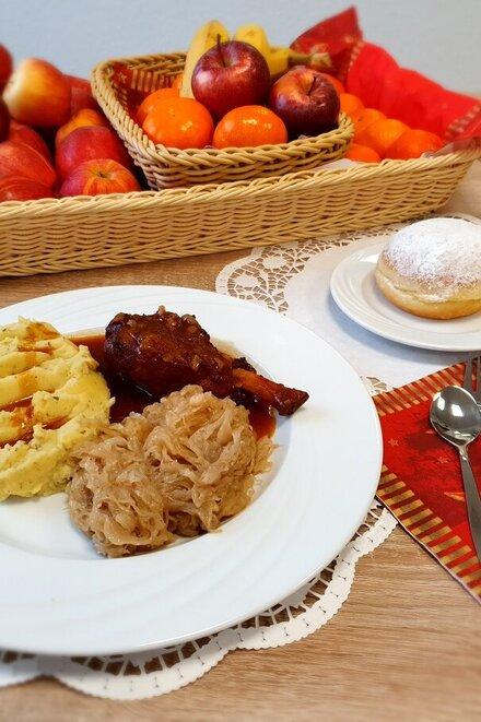 Mittagsmenü bestehend aus Schweinshaxe mit Kartoffelpüree, Kreppel und Obst.
