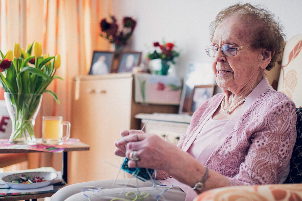 Dame mit Strickzeug im Sessel im Bewohnerzimmer