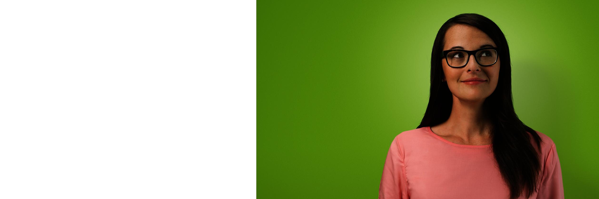 Eine Frau mit Brille auf grünen Hintergrund.