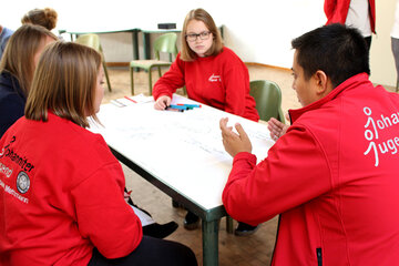 Vier Jugendliche sitzen an einem Tisch mit einer Flipchart in der Mitte und diskutieren
