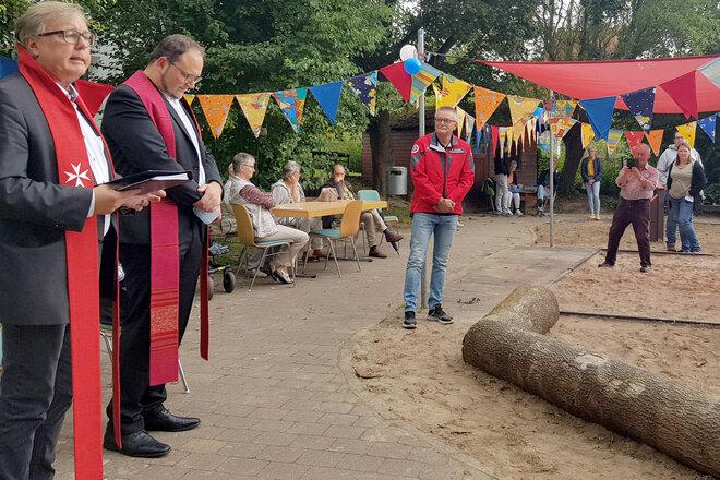 Zwei Pastoren segnen in Anwesenheit von Gästen den Spielplatz