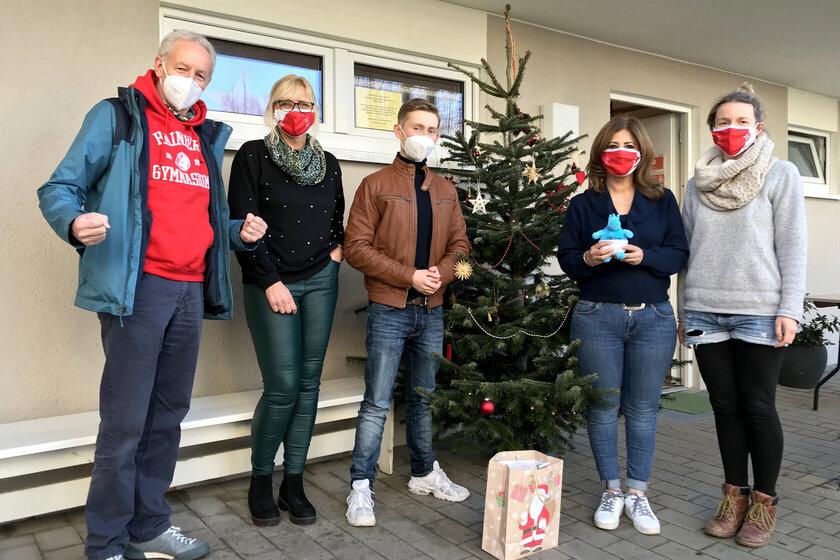 5 Personen stehen draußen am Weihnachtsbaum mit einer Weihnachtstüte