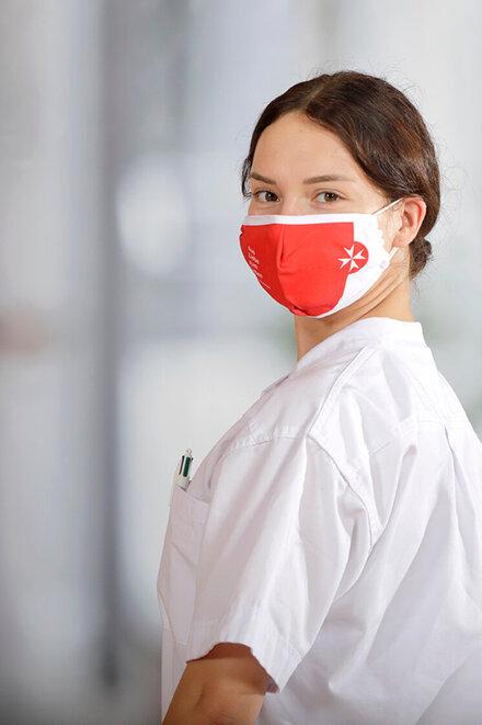 Junge Frau mit weißer Kleidung und Mund-Nasen-Schutz