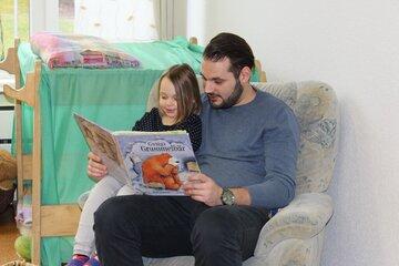 Ein Vater liest seiner Tochter in einem Sessel aus einem Bilderbuch vor.