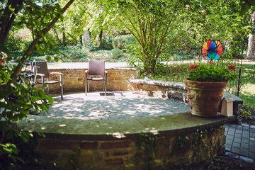 Schattiger Platz mit zwei Stühlen in einer gemauerten runden Einfassung im Garten Johanniterhaus Sinzig