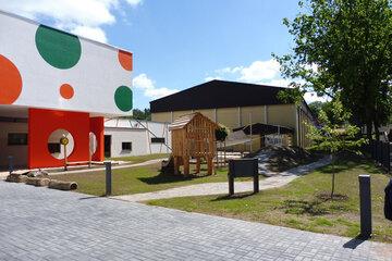 Eingangsbereich und kleiner Spielplatz der Kita mit schönem Holzspielhäuschen.