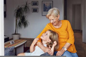 Eine Großmutter mit ihrer Enkelin. Die Oma trägt einen Hausnotruf-Sender am Handgelenk.