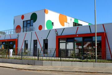 Ansicht der Kita mit ihren aufälligen Punkten in orange und grün von der Straßenseite aus.