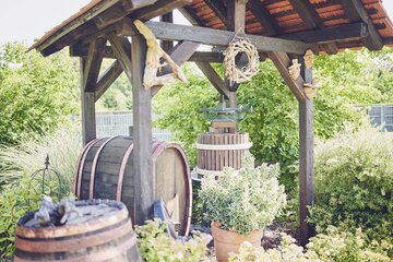 Eine Weinpresse und ein Weinfass im Garten