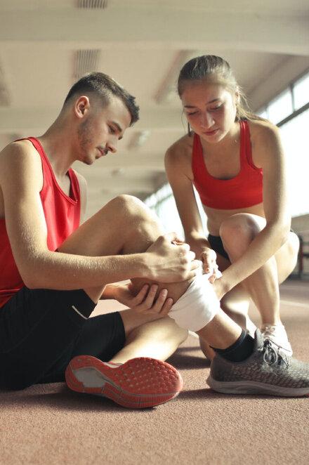Ein junger Mann mit einer Sportverletzung am Bein.