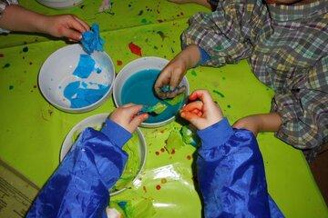 Kinderhände tauchen Papier in blaue Farbe.