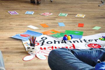 Materialien liegen auf dem Boden vertreut: ein Johanniter-Jugend-Banner, mehrere Pappkarten, Stifte